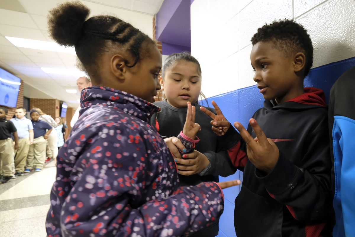 Students interact with one another before class at Thomas Gregg Neighborhood School, an elementary school in Indianapolis, Indiana.