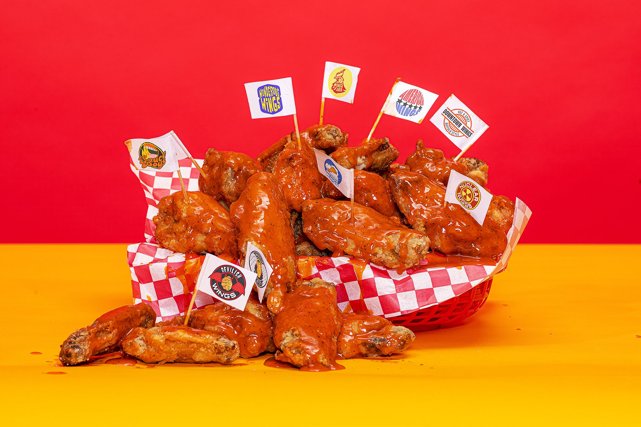 An image of a basket full of wings over a red and yellow background. Several wings have a toothpick planted in them connected to a flag with a different made up chicken wing restaurant logo.