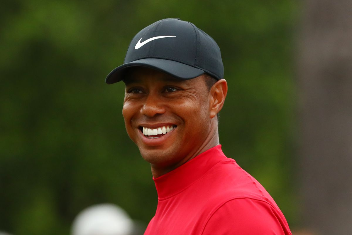 Tiger Woods smiles as he walks off the 8th tee during the final round of The Masters golf tournament at Augusta National Golf Club.