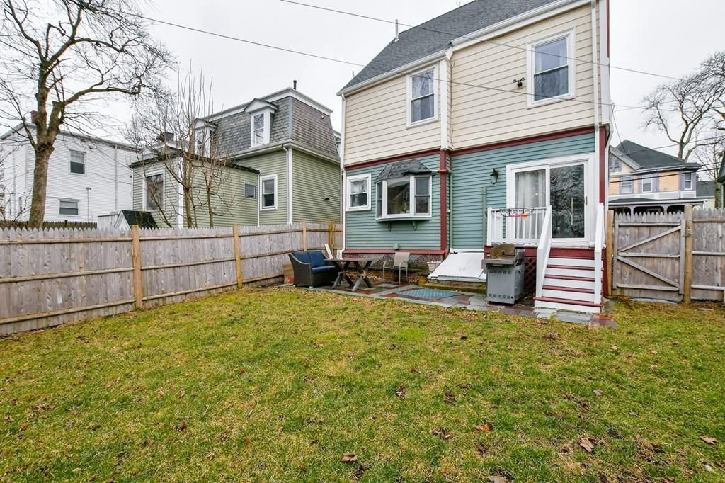 A backyard with a lawn and a patio, all fenced-in behind a house.