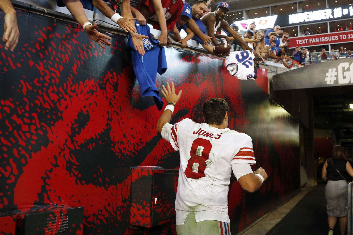 Giants quarterback Daniel Jones high fives fans and runs off the field after defeating the Buccaneers at Raymond James Stadium.