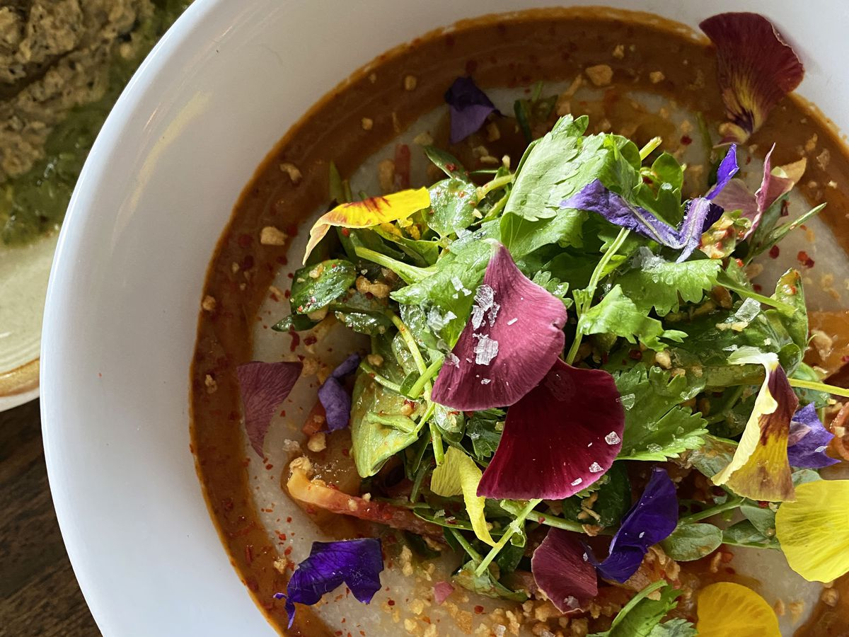 A photo of vegan grits at Hey Love topped with barbecue sauce, roasted pineapple salad, and edible flowers