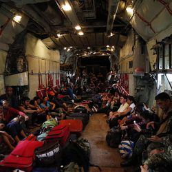 People sit on the floor of a military transport airplane leaving Tacloban, Wednesday, Nov. 20, 2013, following Typhoon Haiyan in the Philippines.