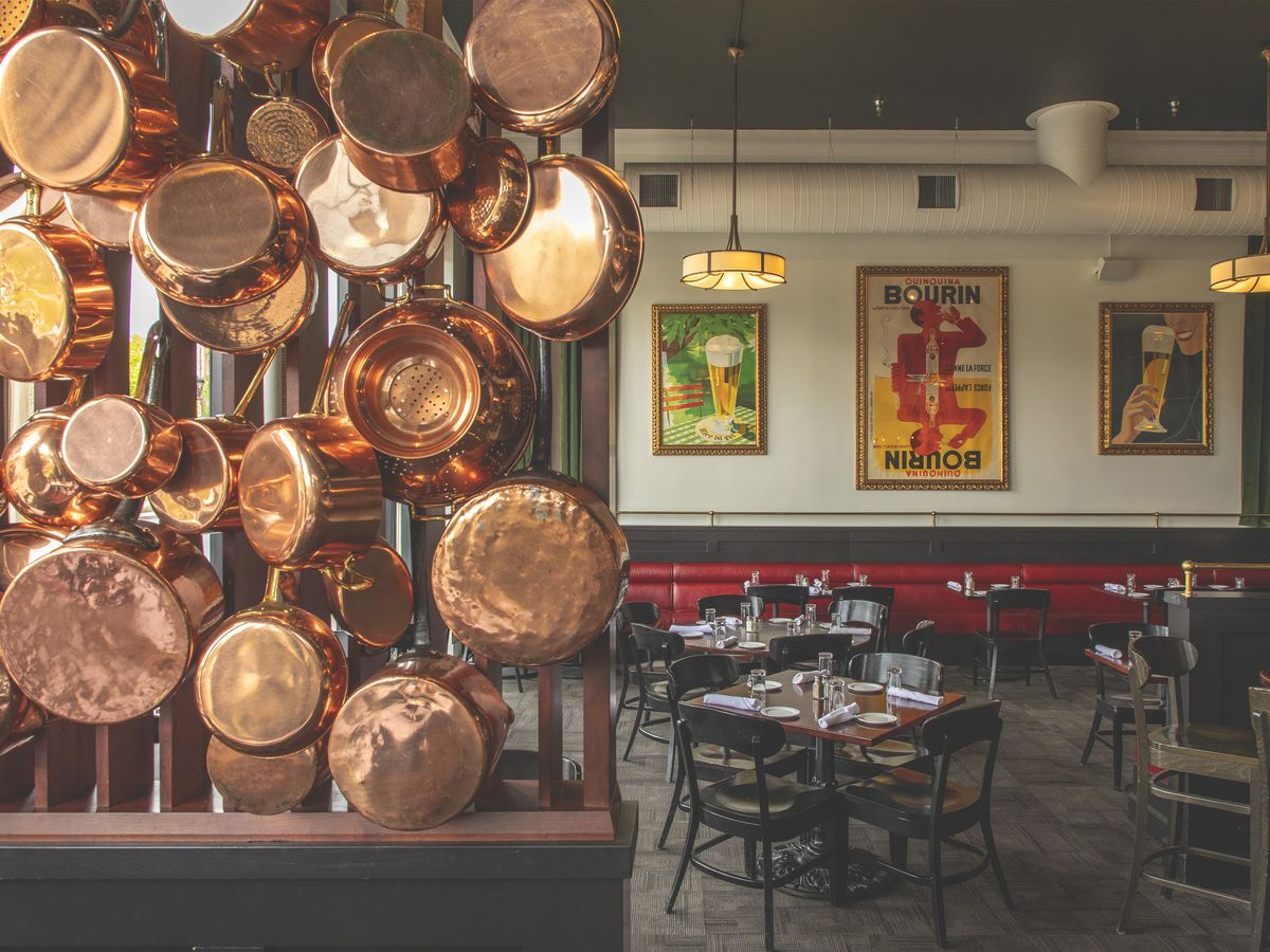 Copper pots hang on the wall inside the dining room at Django