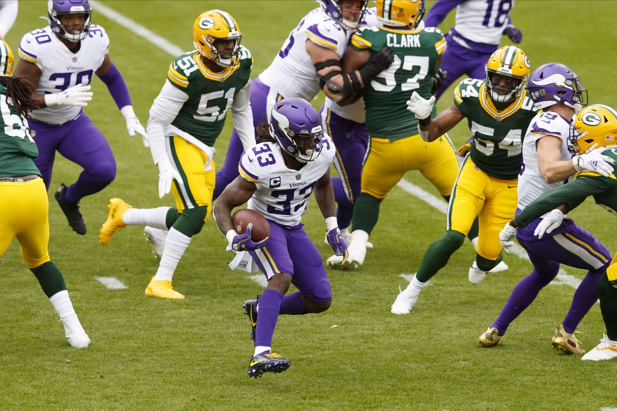 Minnesota Vikings running back Dalvin Cook (33) runs the football against the Green Bay Packers during the first quarter at Lambeau Field.