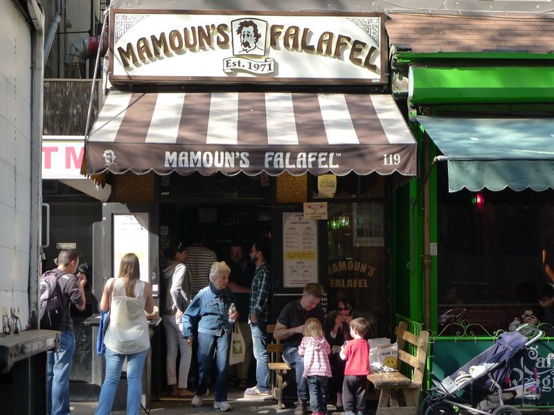 The exterior of Mamoun's Macdougal Street shop, with a brown-and-white striped awning.
