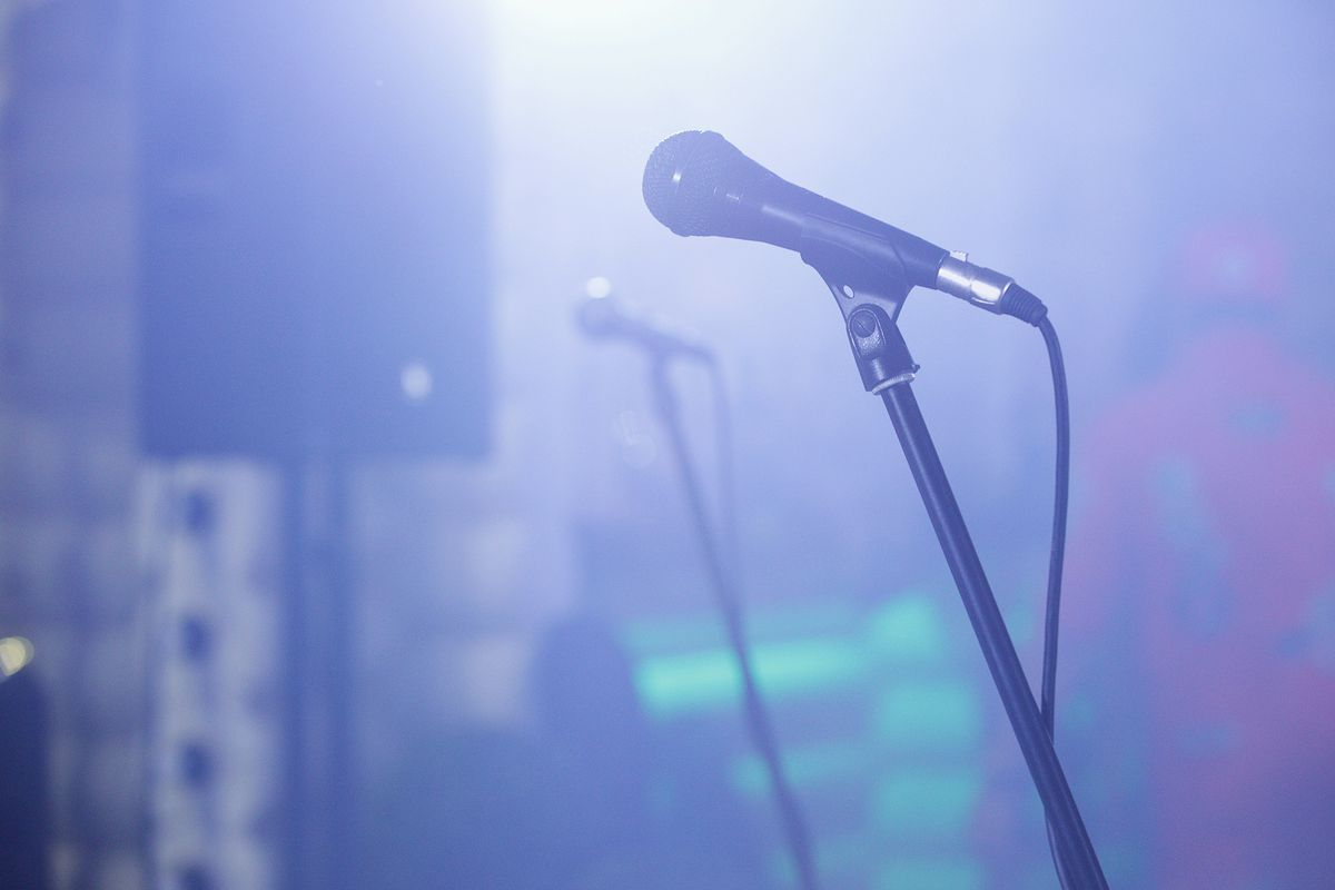 Microphones on stands in a hazy club atmosphere.
