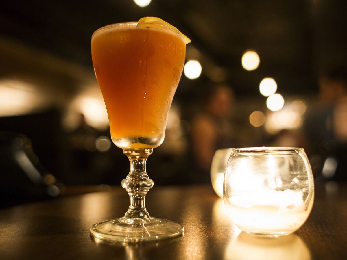The orange-colored cocktail sits next to a glass candle holder on a wooden table in a dimly lit bar.