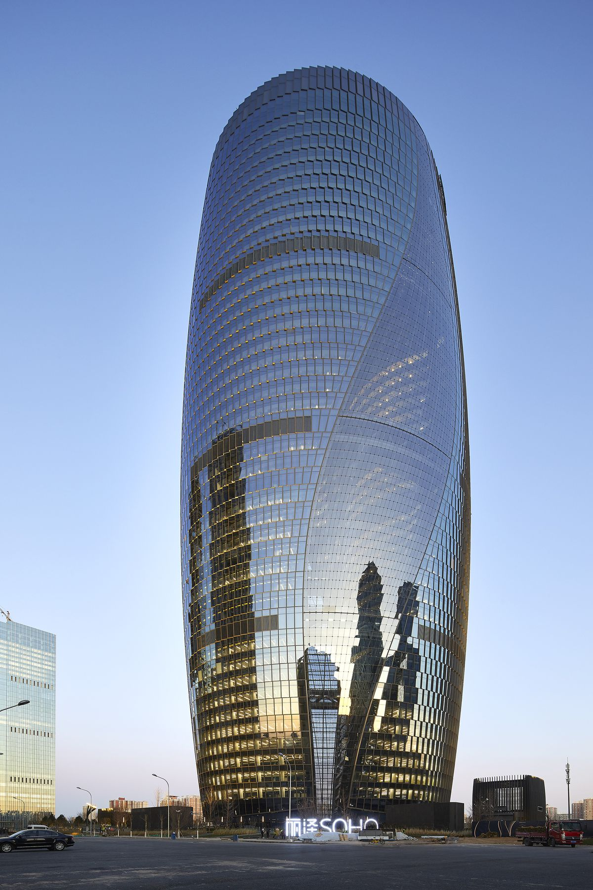 Cylindrical glass tower at dusk.