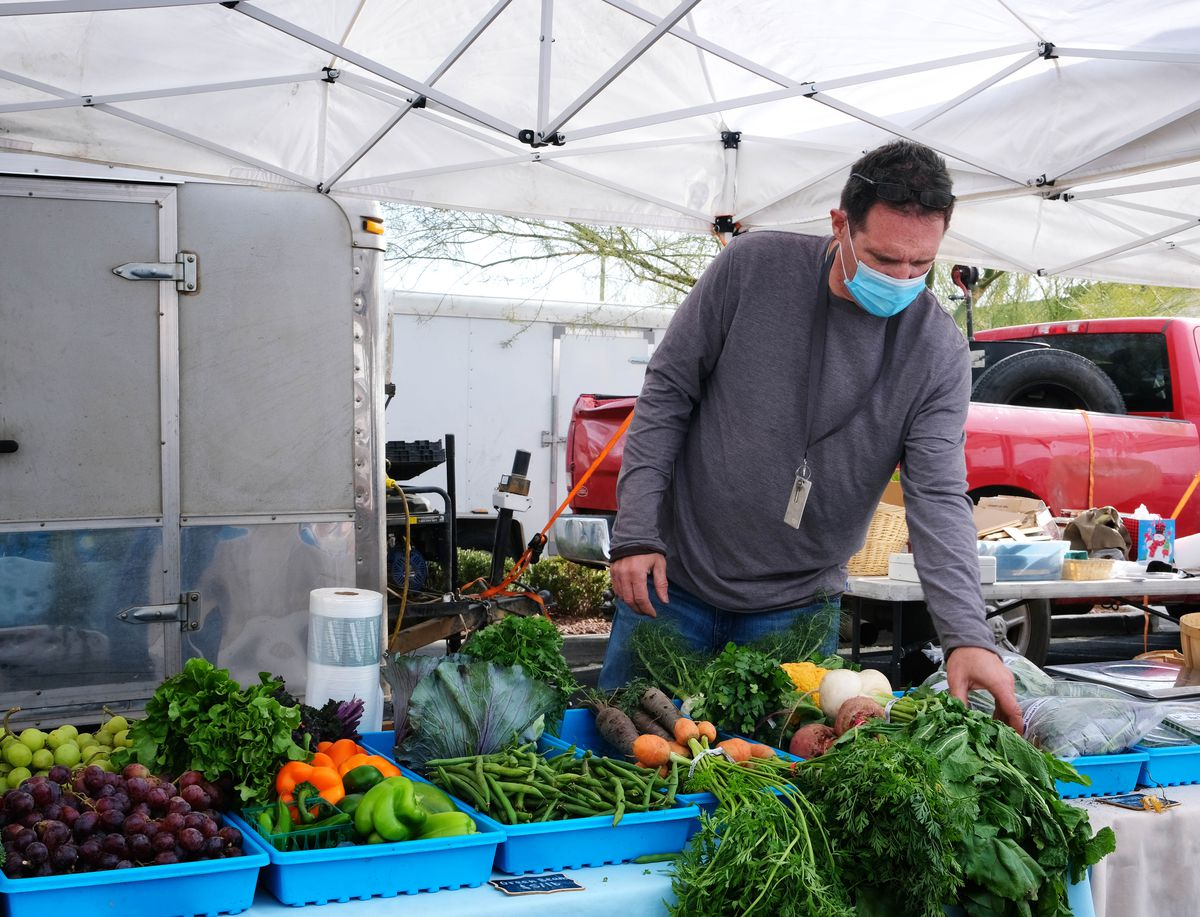 A man wearing a mask works at a produce stand