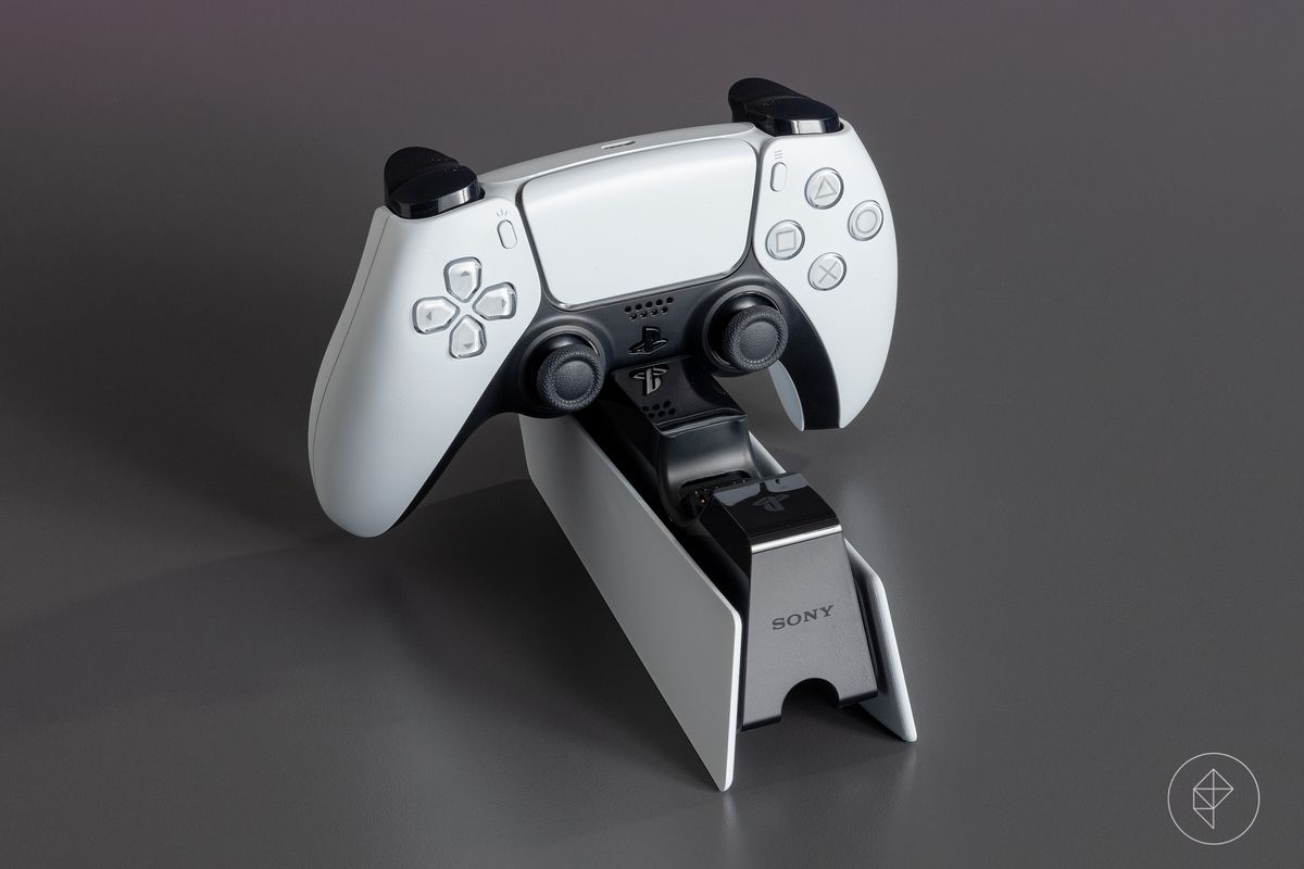 A PS5 controller resting in a charging cradle (not included with console)