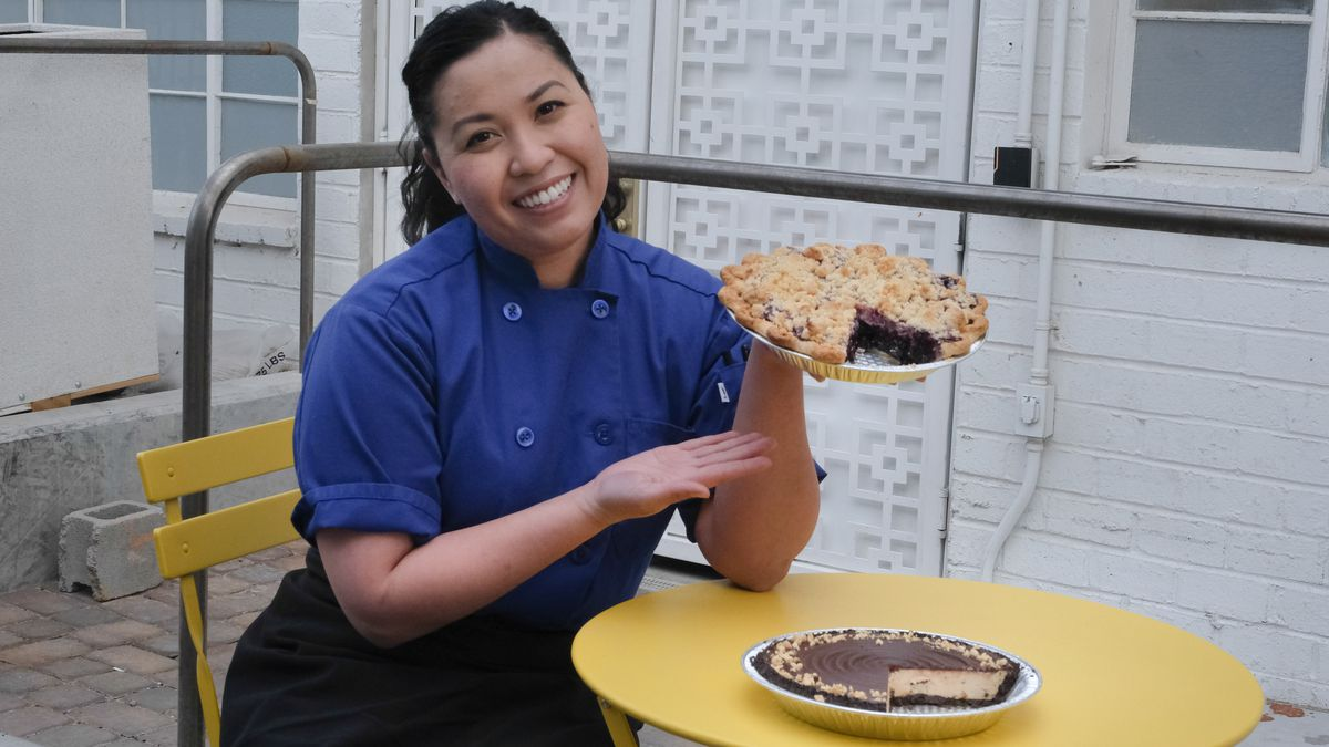 A woman in a blue top and black pants hold a pie in one hand with another sitting on a yellow table.