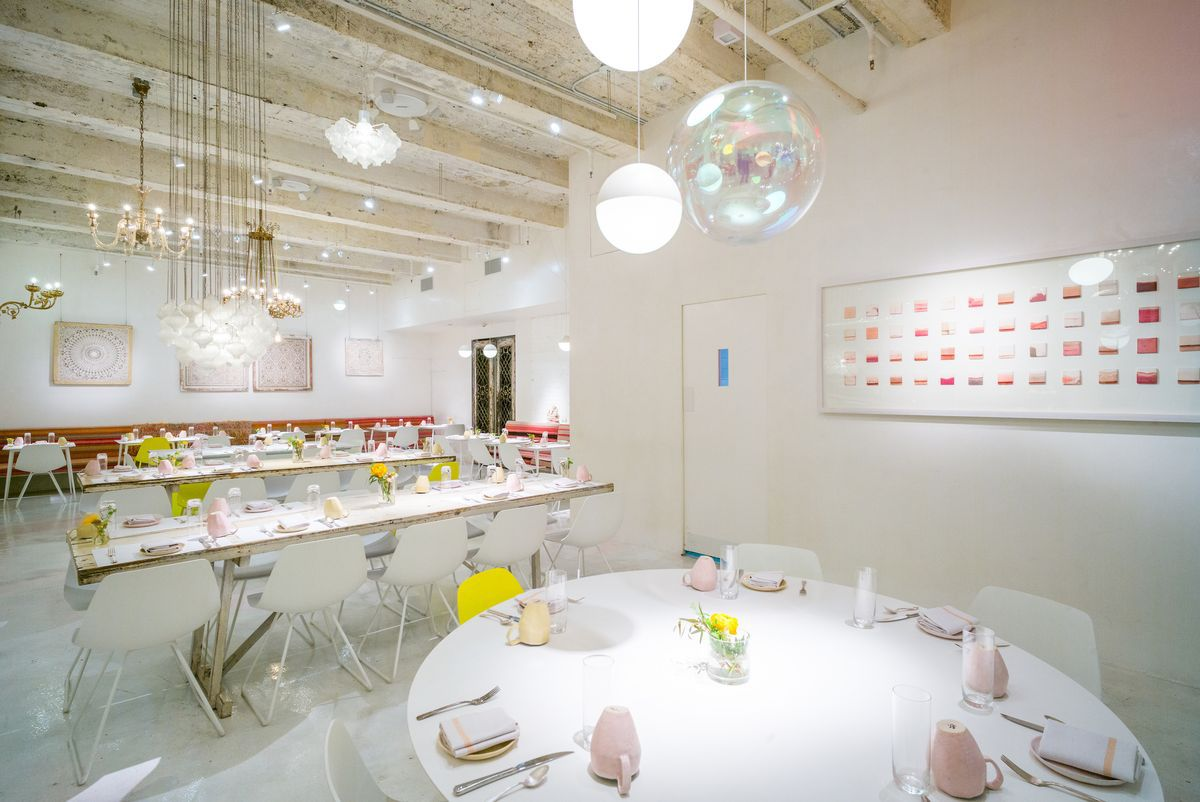 The all-white interior of a restaurant with large communal tables and hanging glass ornaments
