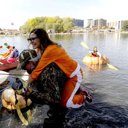 Lindsay Bench gets a little help out of the water as she wanted to stay dry after sitting in one of the pumpkins during the 2013 Mountain Valley Seed Co. Ginormous Pumpkin Regatta at Sugarhouse Park on Saturday, October 19, 2013.
