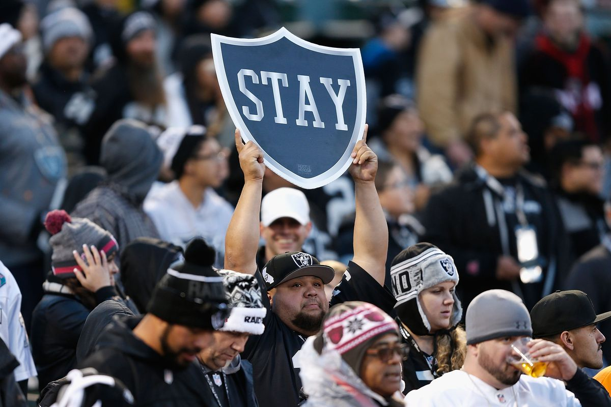 """A Raiders fan holds up a """"Stay"""" sign at Oakland's last home game of the 2015-16 NFL season."""