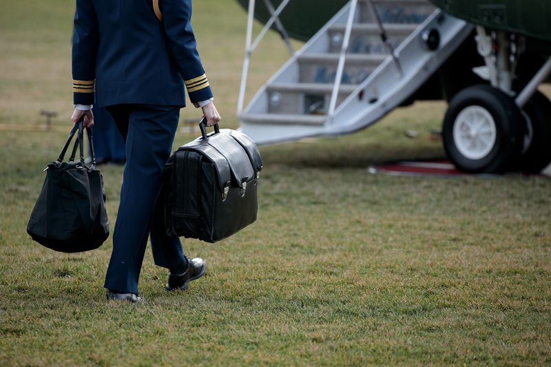 An officer carries a large black briefcase and walks toward an airplane.