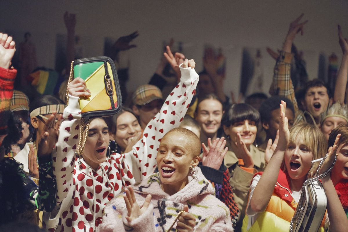 Models wearing rainbow clothing cheer and clap.