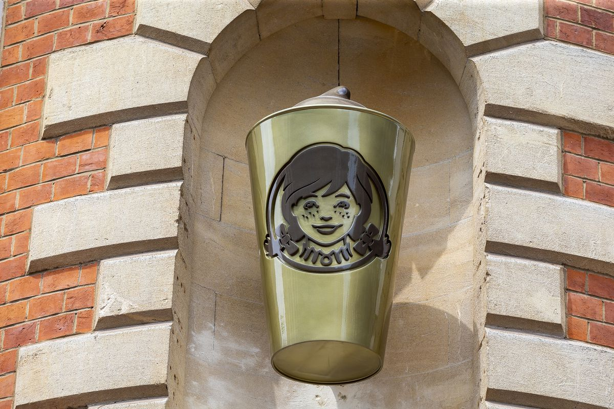 A golden, three-foot tall statue of a Wendy's Frosty drink