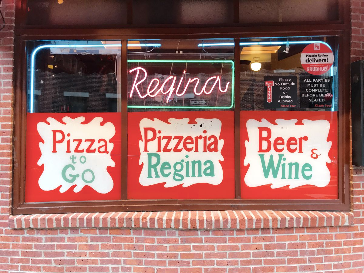 """The exterior window of the original Regina Pizzeria location in Boston's North End includes red and green neon signage that says """"Regina,"""" as well as printed red, green, and white signage reading """"Pizza to Go,"""" """"Pizzeria Regina,"""" and """"Beer & Wine."""""""