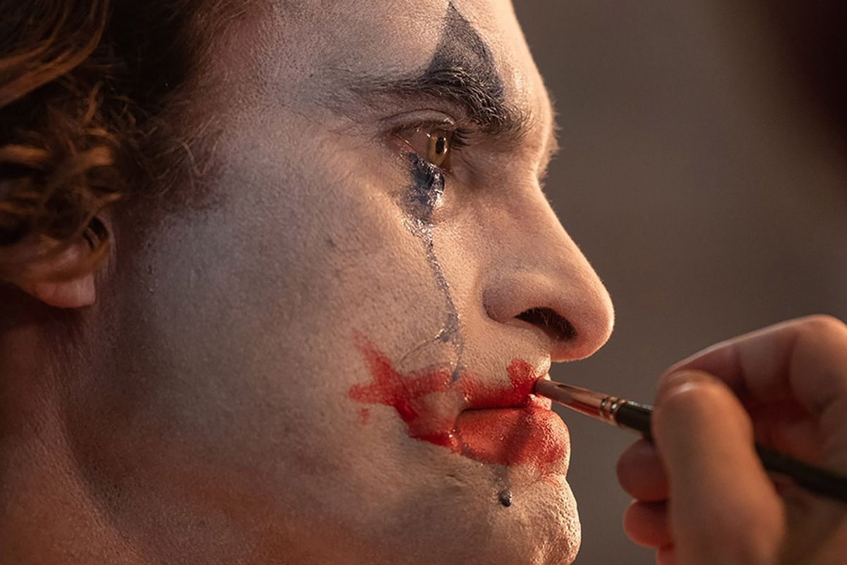 "Joaquin Phoenix applying face paint in the movie ""Joker."""