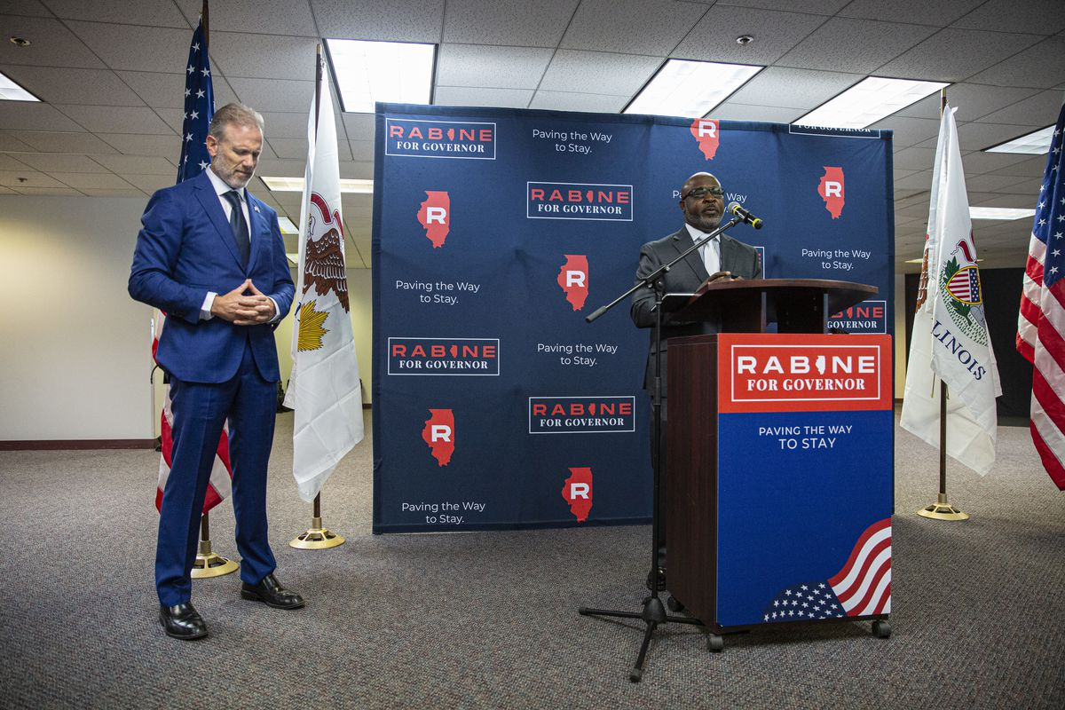 Republican Gary Rabine bows his head down during a prayer at his campaign kick-off at Rabine Group offices Tuesday.