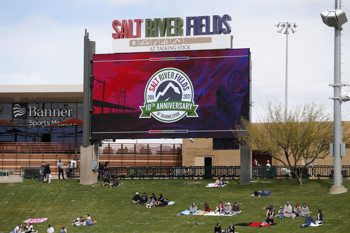 Fans watch from the outfield lawn seating area at Salt River Fields during the Cactus League spring training baseball game between the Colorado Rockies and Arizona Diamondbacks with the Salt River Fields logo, an outline of mountains formed out of a snake, on the jumbotron behind them