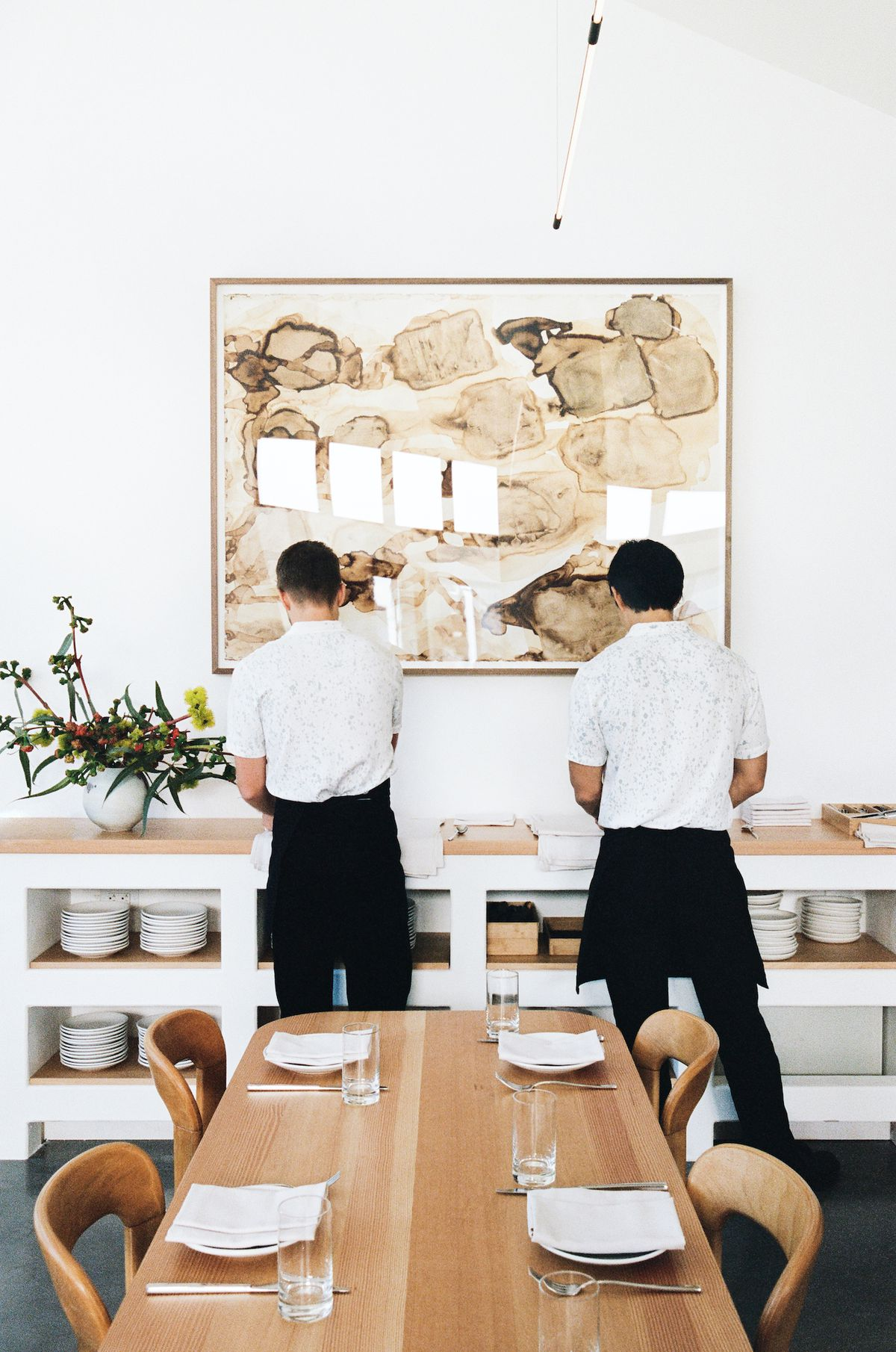 Workers at a service station inside a stark restaurant.