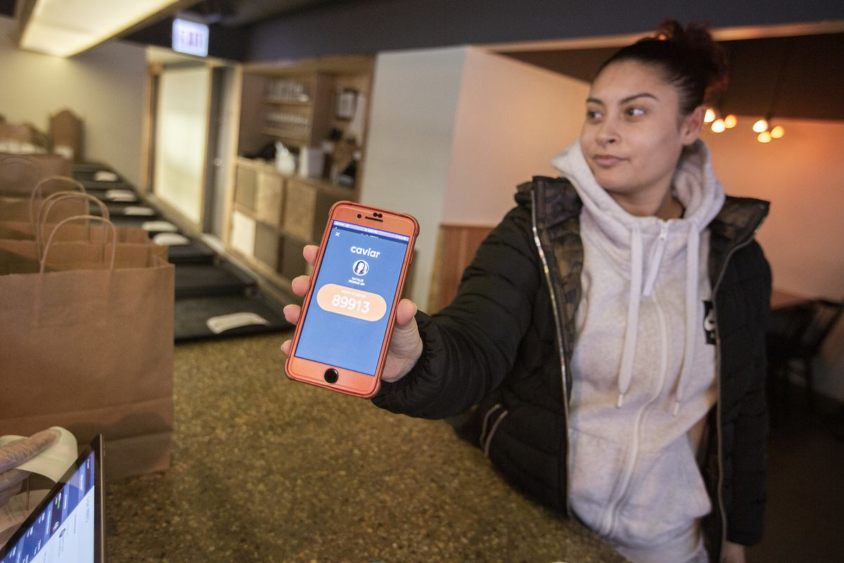 A deliveryperson with a cell phone showing off an app.