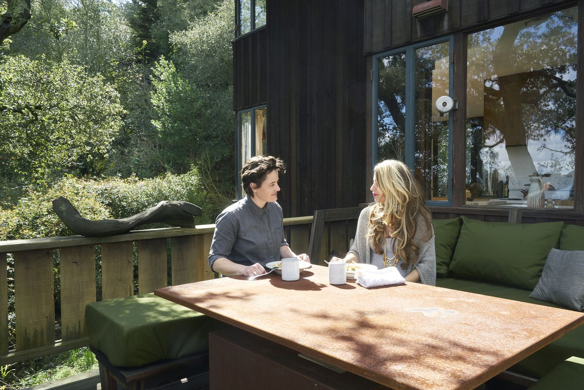 Above: An office has a long desk shared by both women; it sits under a large bay window. Below: The two women sit outside on their large deck.
