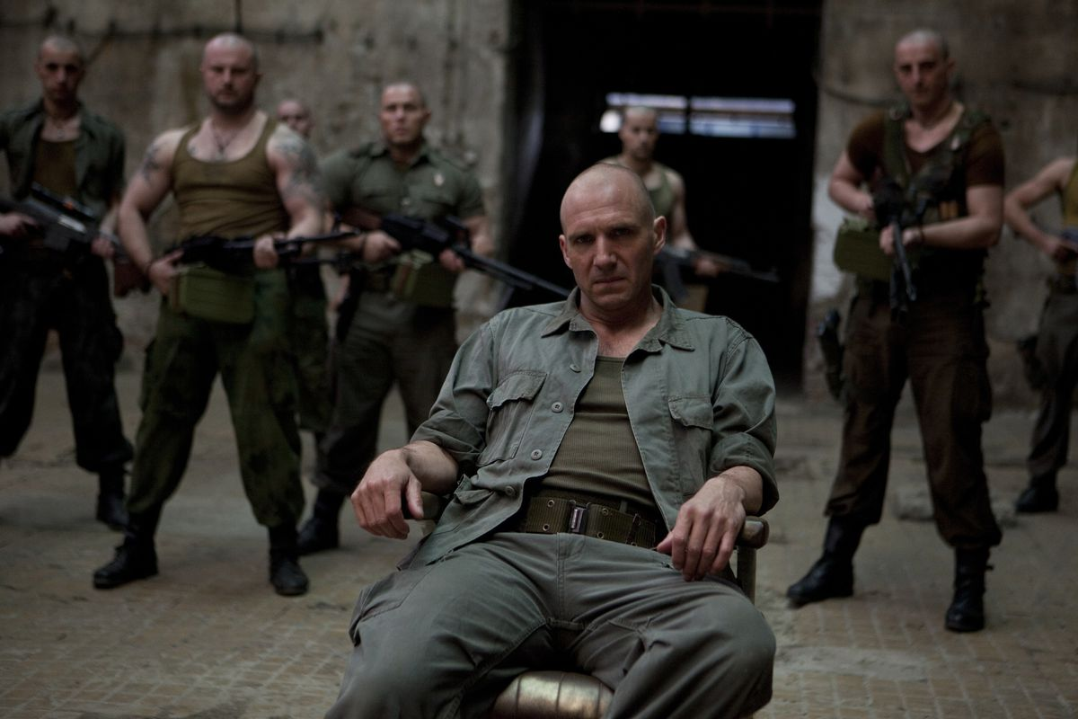 Coriolanus (Fiennes) sits surrounded by his soldiers, all of whom wield guns.
