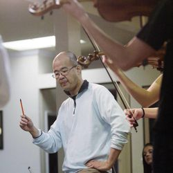 Gifted Music School director Eugene Watanabe works with the school's orchestra in Salt Lake City on April 13, 2014.