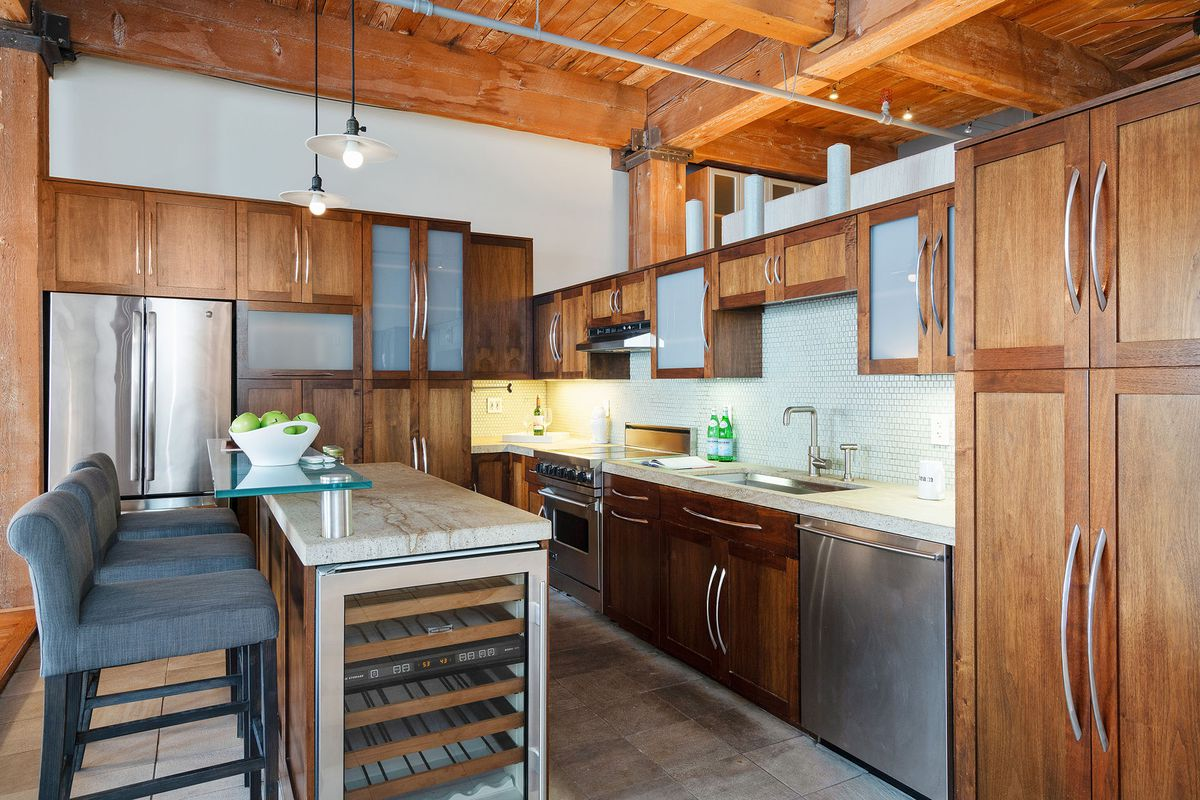 A kitchen has wood cabinets, a wine fridge, and gray bar stools at a small island.