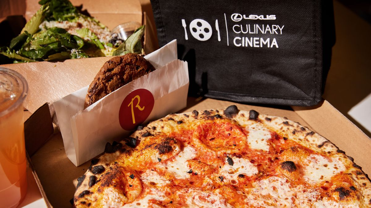 """A pizza, chocolate cookie, and salad sit next to a black tote bag that reads """"Lexus Culinary Cinema."""""""