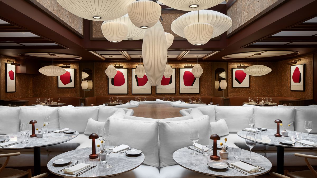 A large white couch is the centerpiece of a dark dining room filled with abstract art at Lyle's