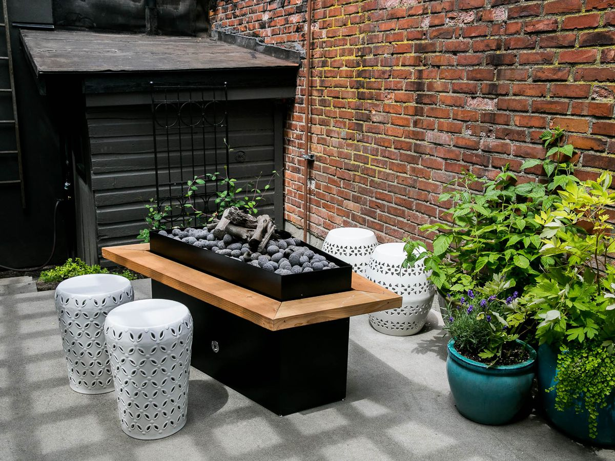 A look at outdoor seating at Brimmer and Heeltap, with a brick facade and plants surrounding a small charcoal pit.