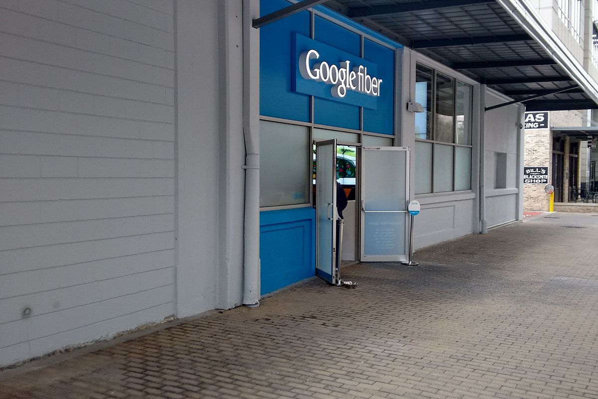 Sidewalk with a white building on left that has a blue Google sign above an open doorway halfway down