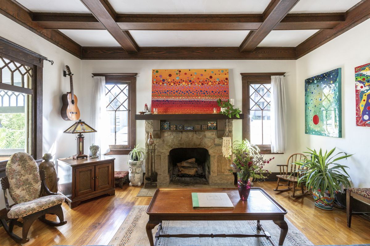 Room features stone fireplace, wooden floors, and art on walls.