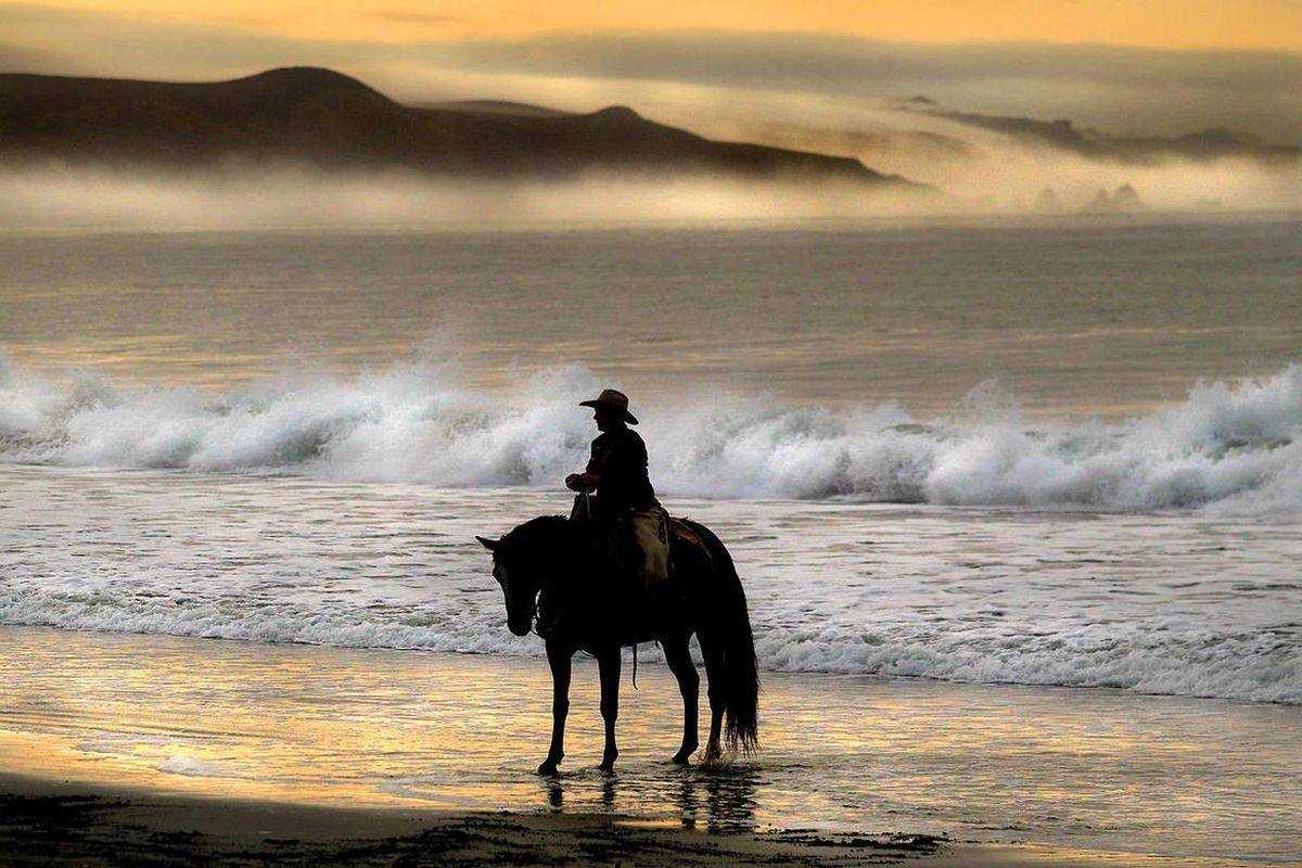 Eddy Ann Filipini of Battle Mountain, Nevada, waits in the surf at Doran Beach in Bodega Bay Friday, Sept. 26, 2014 for the start of a horse relay ride across the United States to protest grazing rights in her state.