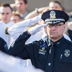 Officers salute as Unified police officer Doug Barney's casket is placed into the hearse following funeral services at the Maverik Center in West Valley City on Monday, Jan. 25, 2016.