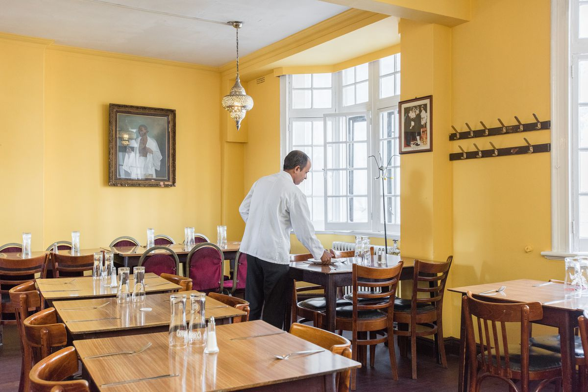 A waiter tends a table inside the India Club on the Strand in central London