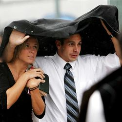Katie Keiser and Brandon Finenco hurry out of the Conference Center and into the rain after the first session of conference Saturday.