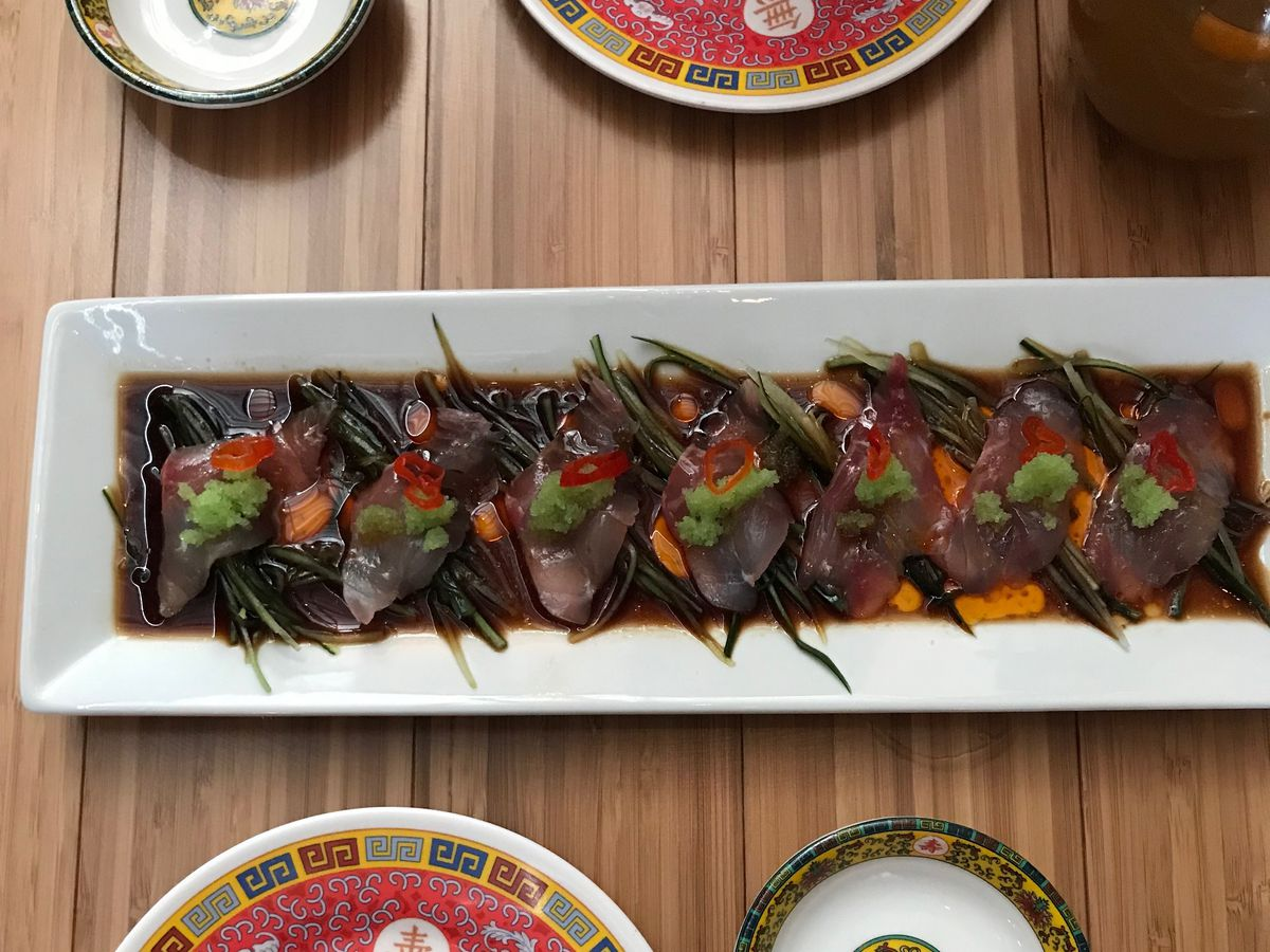 A long dish with pieces of cured fish lying in ponzu and sesame oil sauce, arranged beneath garnishes of Japanese cucumber and slices of limo chile pepper