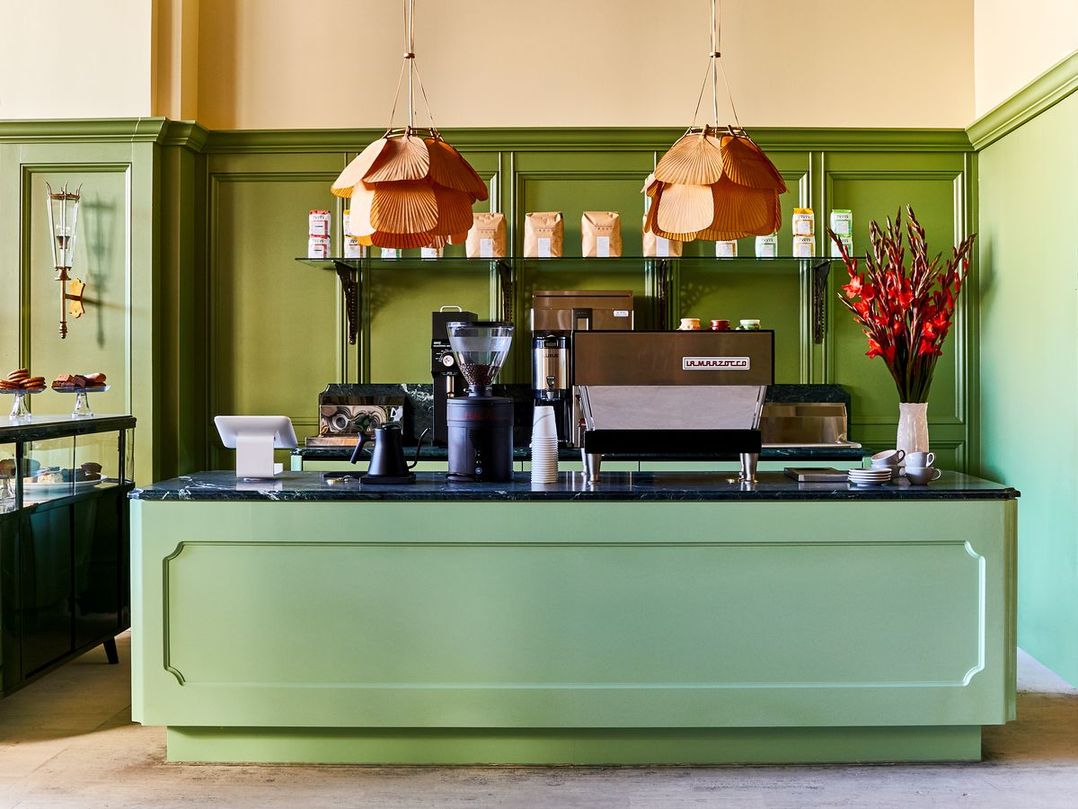 The small coffee bar at Populace is mint green with fan-like tan pendant lights and a vase of red flowers.