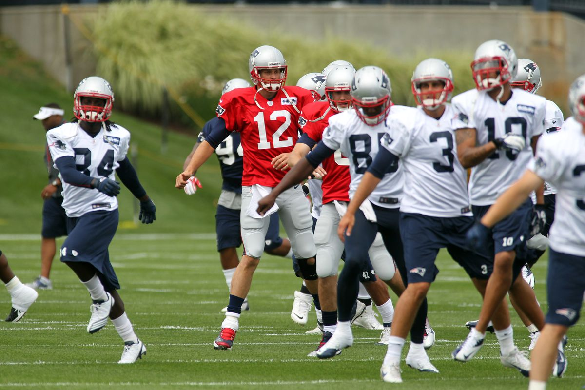 July 26, 2012; Foxborough, MA, USA; New England Patriots  quarterback Tom Brady (12) and the rest of the team warm up during the Patriots opening day of training camp at the team practice facility. Mandatory Credit: Stew Milne-US PRESSWIRE