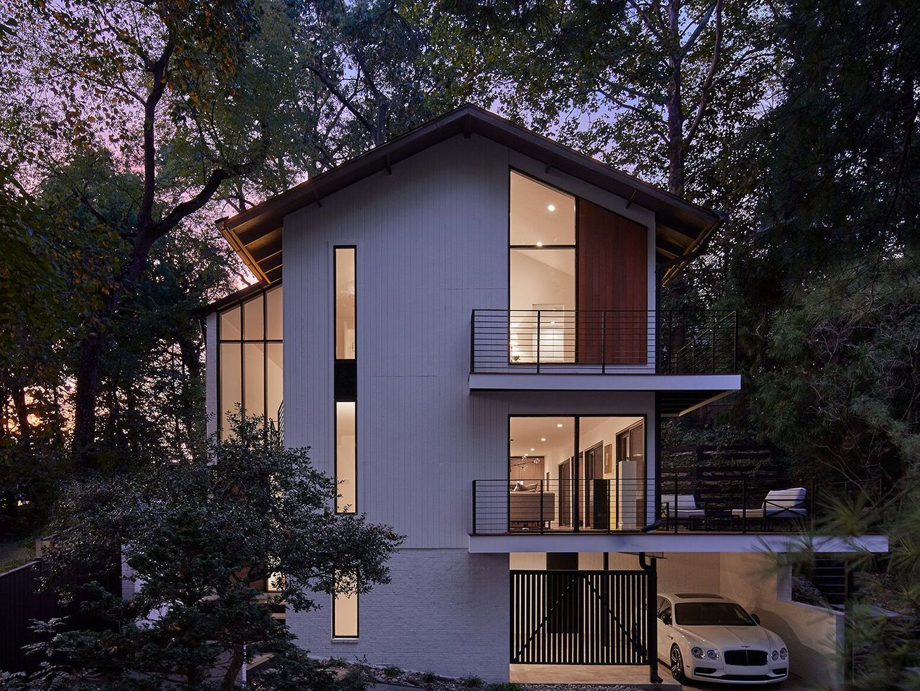 Front of house at dusk, featuring pitched roof and two levels of decks.