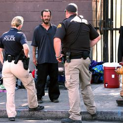 Law enforcement officials talk to a homeless man as they conduct Operation Rio Grande in Salt Lake City on Monday, Aug. 14, 2017.