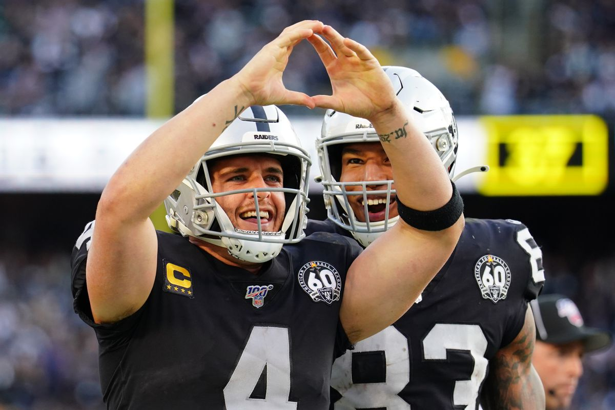 Derek Carr of the Oakland Raiders celebrates a first down with Darren Waller during the second half against the Jacksonville Jaguars at RingCentral Coliseum on December 15, 2019 in Oakland, California.