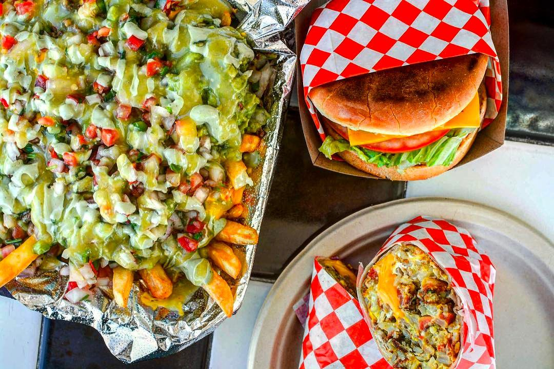 Loaded fries with guacamole, a burger, and breakfast burrito.