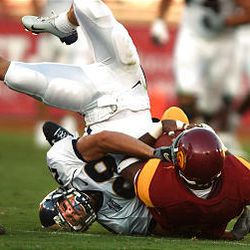 BYU receiver Chris Hale tackles USC defender Marcell Allmond after Allmond intercepted a Matt Berry pass during Saturday's contest at the Los Angeles Coliseum.