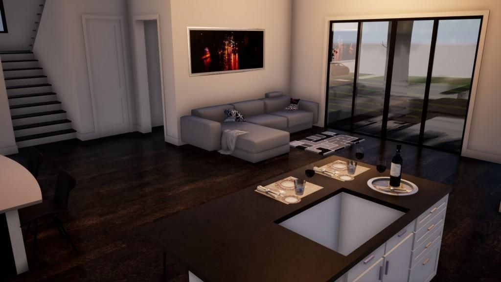A living room with white walls and a kitchen next to it.